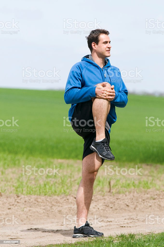 man stand and stretch the leg stock photo