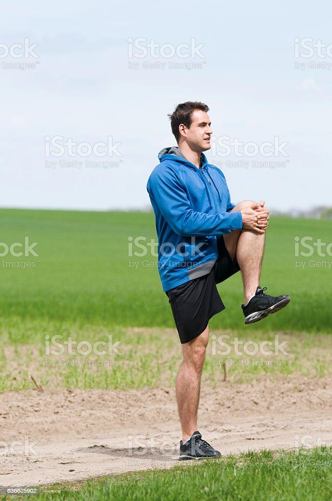 man stand on one leg stock photo
