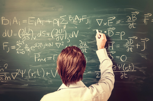 Man standing against chalkboard, solves physics equations, rear view, retro