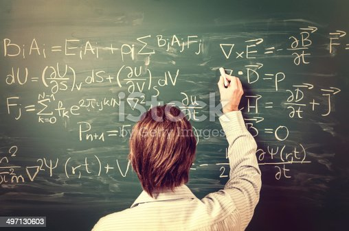 Newton's Equations. Rear view, close-up on young man standing back against green chalkboard. He explains, solves physics tasks, retro style. Processing for retro bleached look, slight vignette added.
