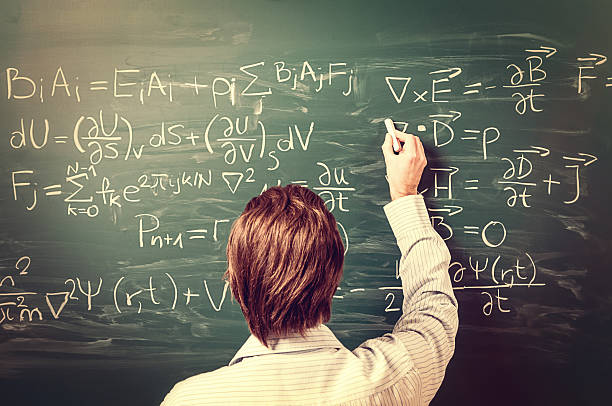 Man standing against chalkboard, solves physics equations, rear view, retro stock photo