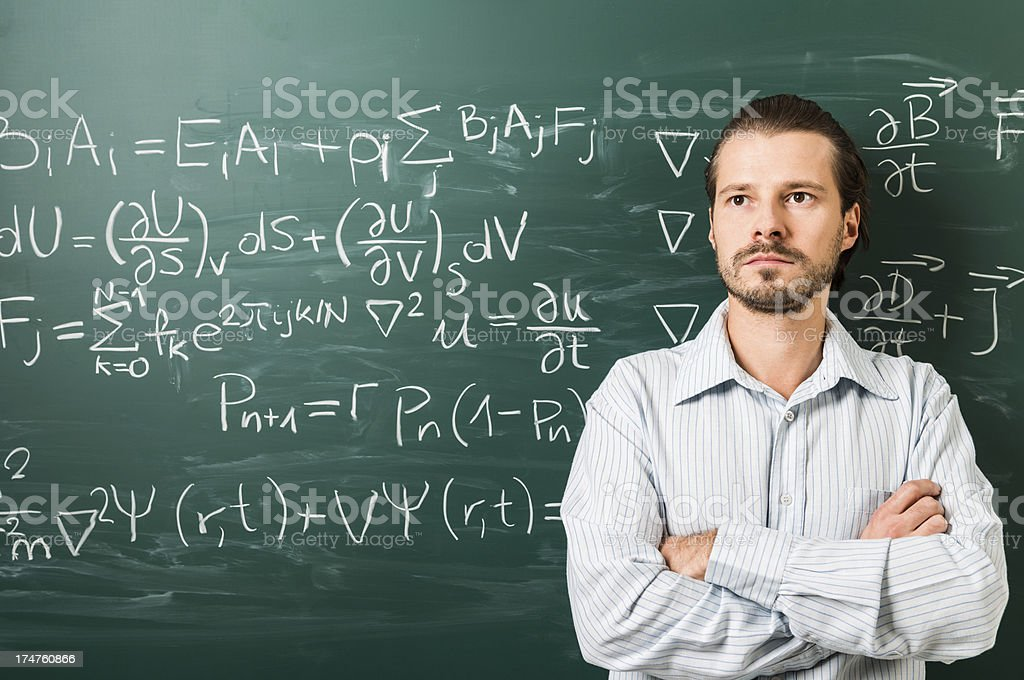 Man standing against mathematical formula on green chalkboard royalty-free stock photo