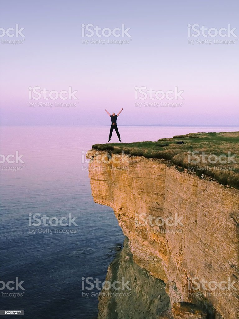Man standing all with arms up and open at the edge of cliff royalty-free stock photo