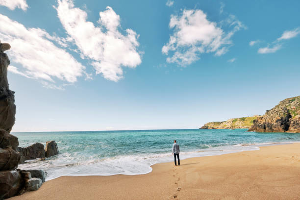 man standing alone at the shoreline of pedn vounder beach, cornwall on a bright sunny morning. - cornwall stock pictures, royalty-free photos & images