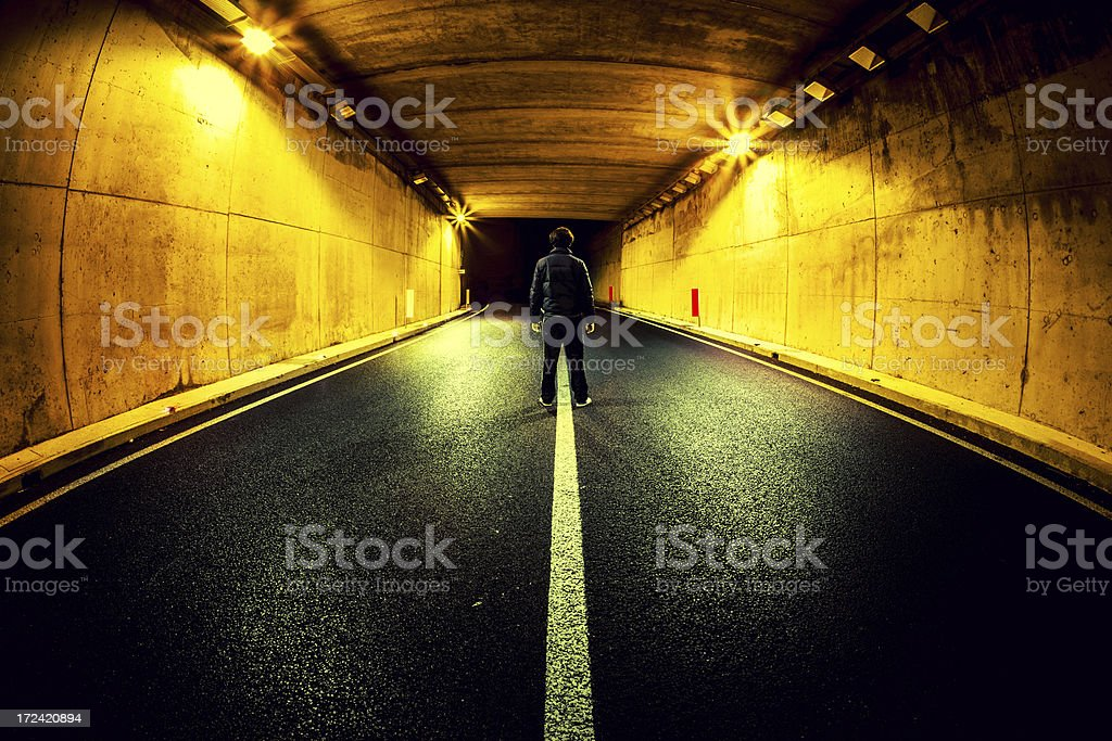 Man Standing Alone in Middle of Road Tunnel at Night stock photo