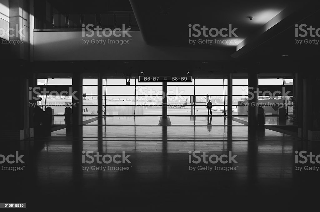 man standing alone in the ben gurion airport stock photo