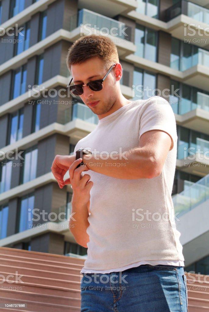 Homem de pé sozinho na escada. Rapaz bonito com óculos de sol, olhando para o relógio de pulso. Masculino modelo posando para fotografar em etapas. Retrato de cara fique na escada, detalhe de moderno edifício no fundo. - foto de acervo