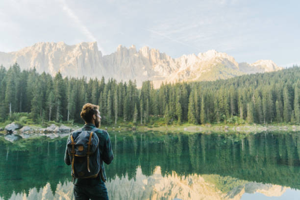 man standing and looking at  lago di carezza in dolomites - latemar foto e immagini stock