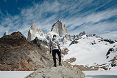 Young Caucasian man in white jacket standing on the rock and enjoy the scenic view of Mount Fitzr Roy near Laguna de los Tres in Patagonia