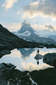 Man standing and  looking at scenic view of lake near Matterhorn mountain