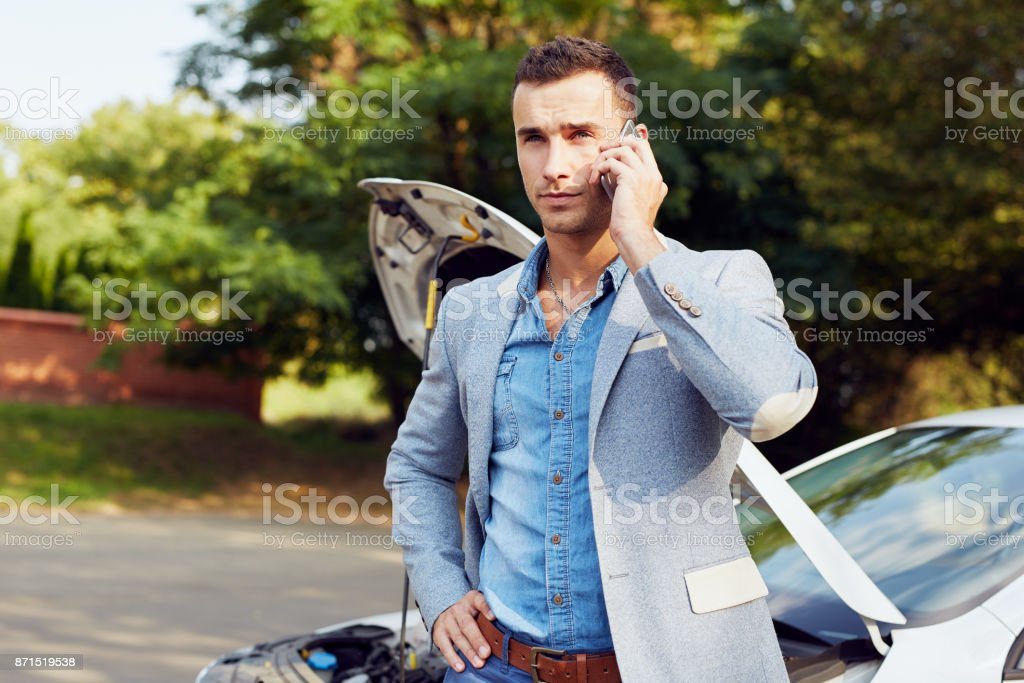 Man standing at a broken car and calling stock photo