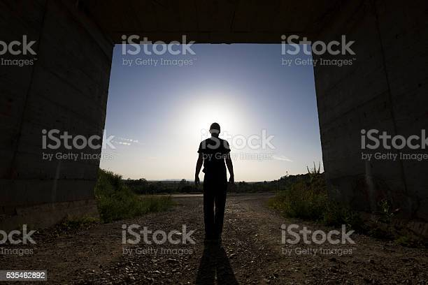 Photo of Man standing at large passage of concrete building, blocking sunlight