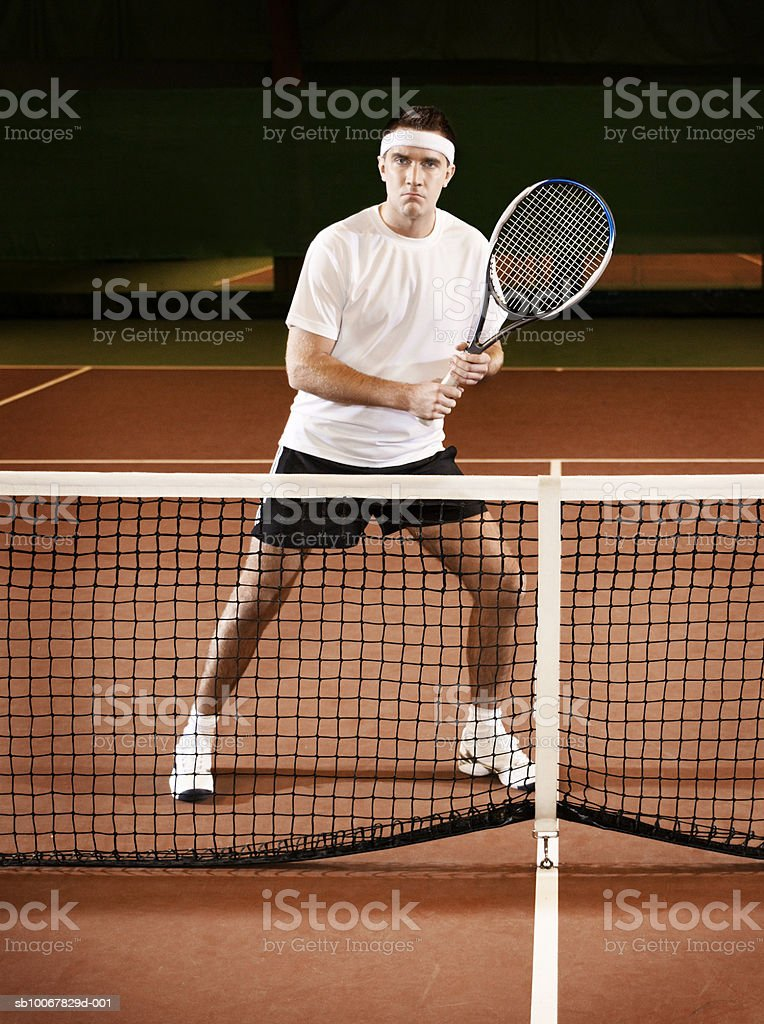 Man standing at net with tennis racket foto de stock royalty-free