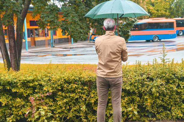 A man standing at the bus station with an umbrella waiting for a bus. Rainy day in a local town stock photo
