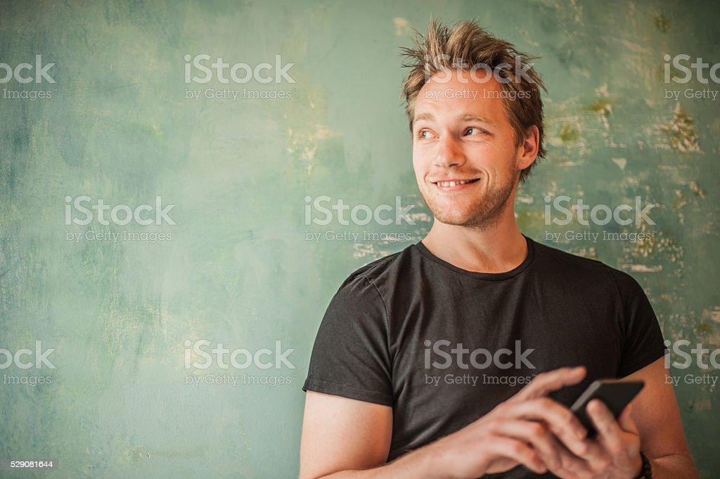 Uomo in piedi al muro, scrittura messaggio e guardando lontano - foto stock
