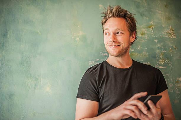 hombre parado en la pared, de la escritura mensaje y mirando lejos - un solo hombre joven fotografías e imágenes de stock