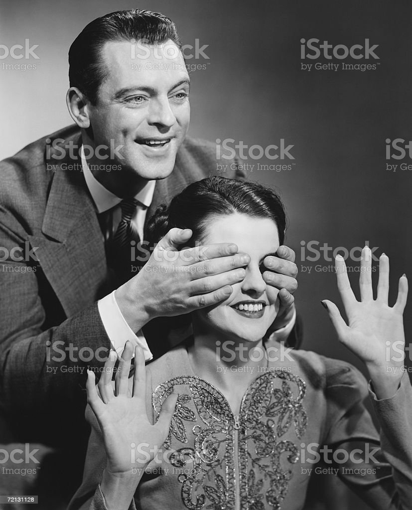 Man standing behind woman, covering her eyes (B&W) stock photo