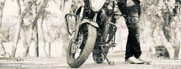 Photo of Man standing beside a modern motorbike