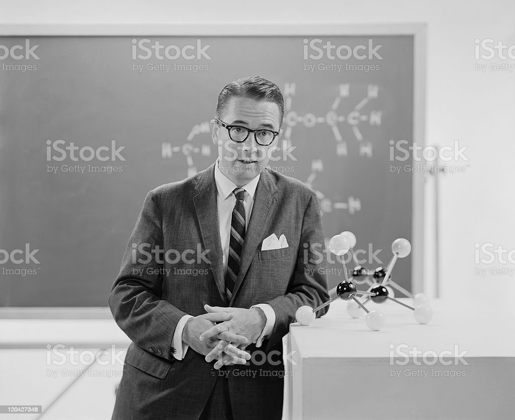 Man standing beside molecule model, portrait stock photo