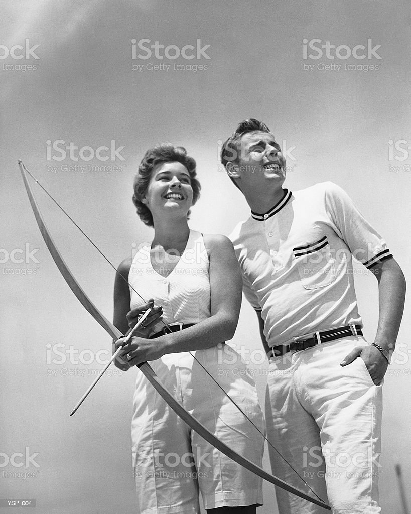 Man standing beside woman who is holding bow and arrow royalty-free stock photo