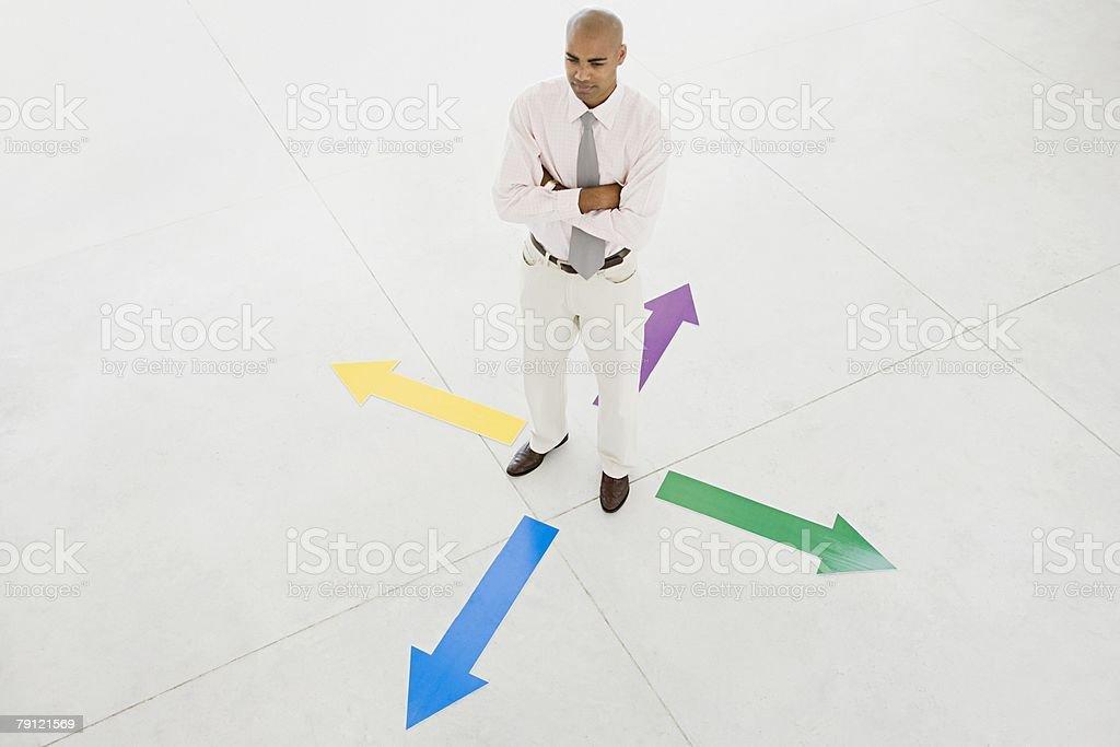 Man standing between arrows stock photo