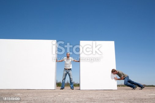 istock Man standing between two walls pushing outdoors with adversary 181549499
