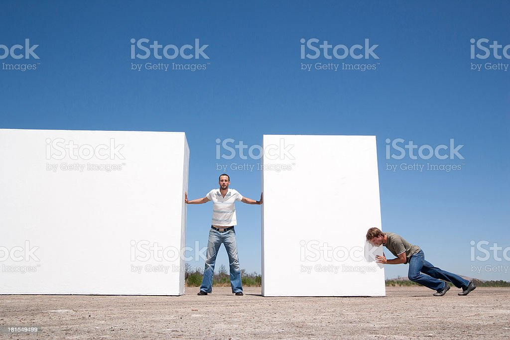 Man standing between two walls pushing outdoors with adversary stock photo