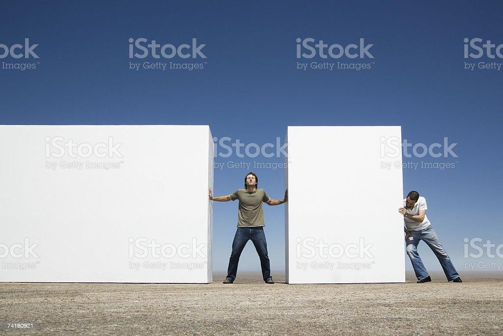 Homem de pé entre duas paredes de empurrar ao ar livre com Adversário foto de stock royalty-free
