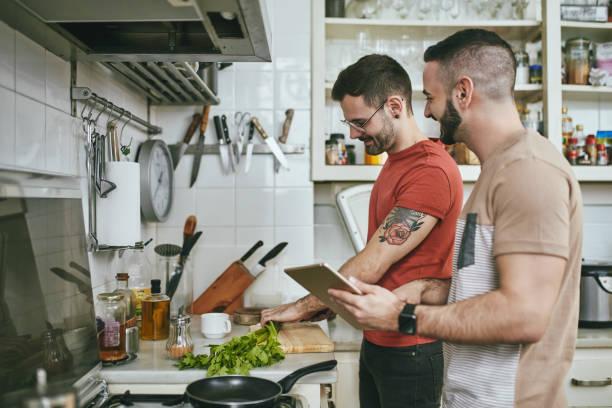 Mann steht bei einem Freund, der zu Hause Essen zubereitet – Foto
