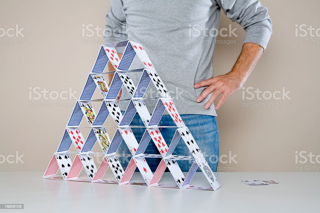 Man standing by house of cards stock photo