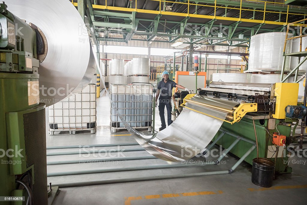 Man standing by large roll of aluminium in factory stock photo