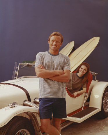 A young couple with an Excalibur Roadster loaded with two surfboards.
