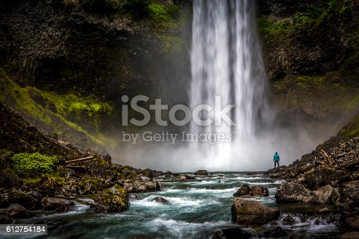 istock Man standing close to huge waterfall. 612754184