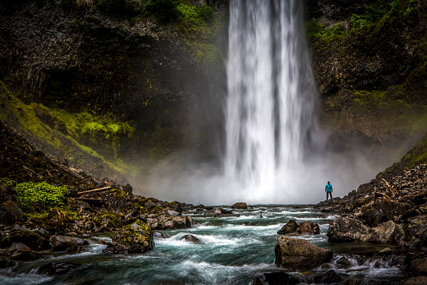 Man standing close to huge waterfall. Athletic male standing on rocks at the bottom of waterfall. british columbia stock pictures, royalty-free photos & images