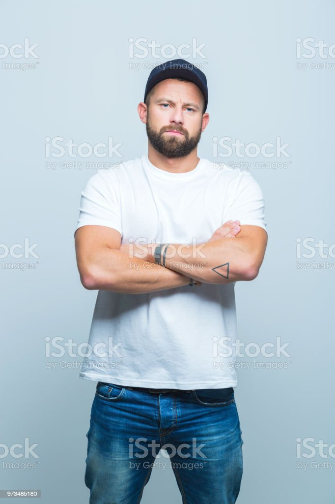 Man standing confidently Portrait of handsome young man with beard standing with his arms crossed and looking at camera. Adult Stock Photo