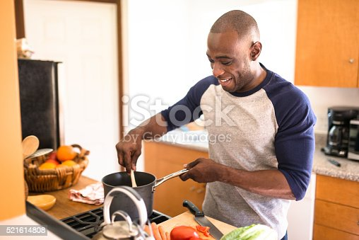 istock man standing happiness on the kitchen and preparing food 521614808