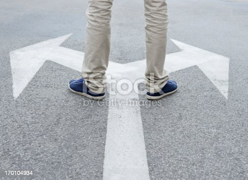 Man standing on arrows painted on asphalt.