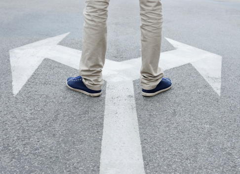 Man standing on arrows painted on asphalt.