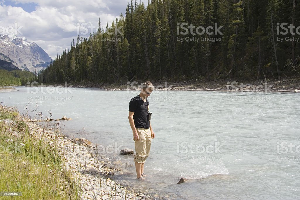 man standing in a cold river royalty-free stock photo