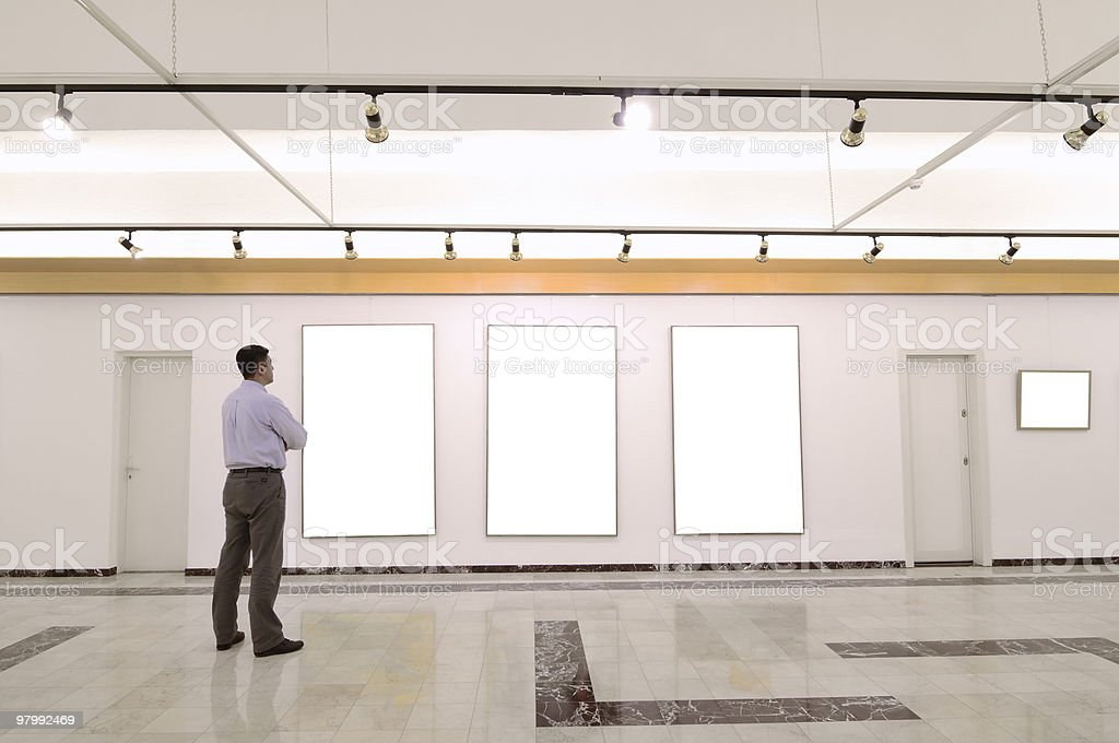 Man standing in a gallery looking at three blank displays royalty-free stock photo