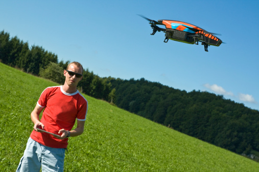 A man is playing with a Drone, the quadricopter is controlled by an touch pad by using a wifi connection. The drone is equipped with two camera designed to capture HD front of and below the drone.