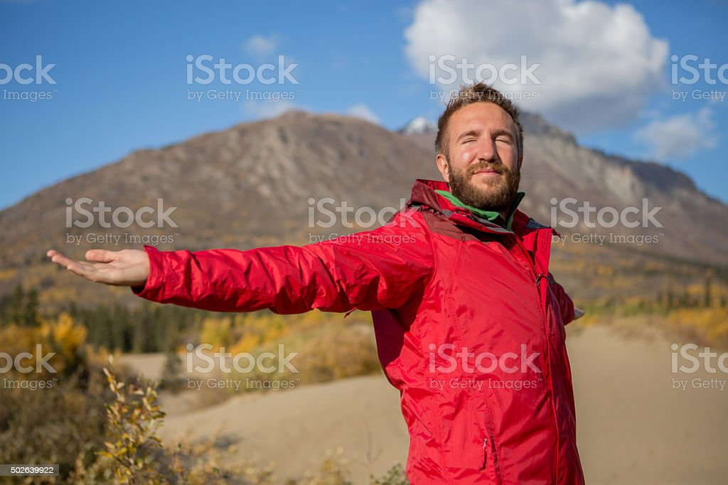 Man standing in desert arms outstretched for positive emotion stock photo