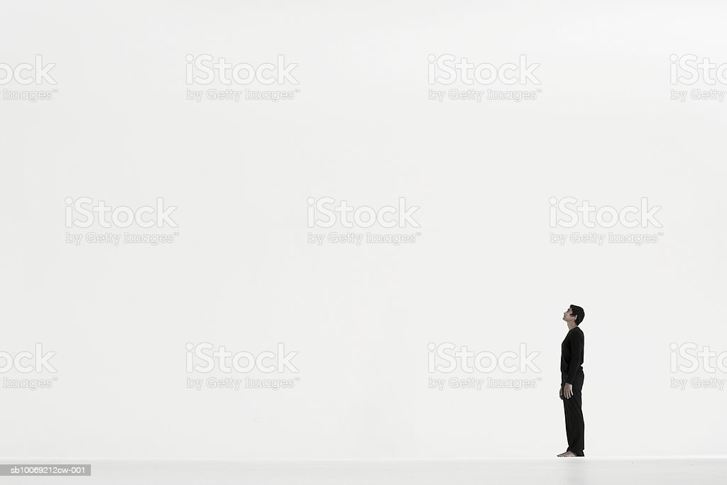 Man standing in distance against white background, side view 免版稅 stock photo