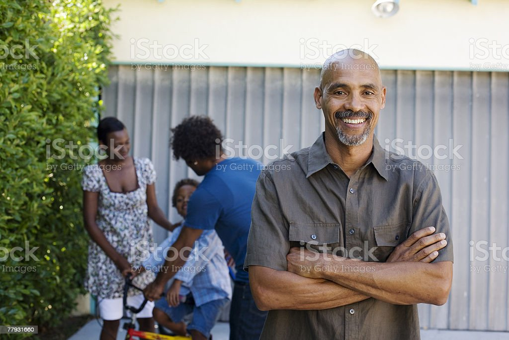 Man standing in driveway with people in background stock photo