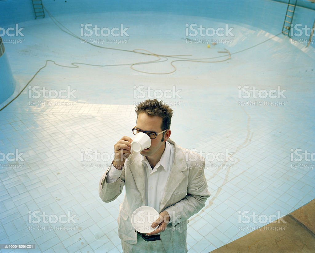 Man standing in empty pool, drinking tea, elevated view royalty-free stock photo