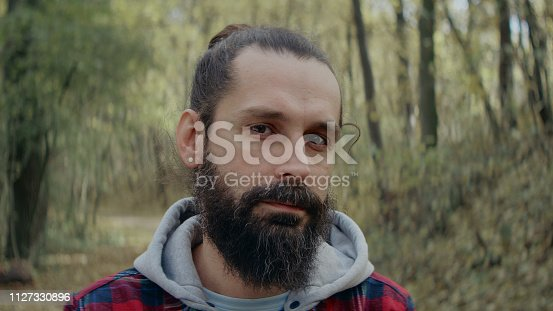 Young man standing in the forest. Looking at camera