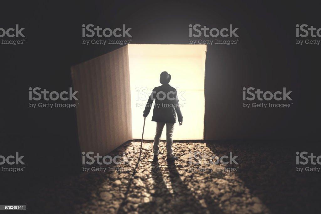 man standing in front an open lightened door in the dark stock photo