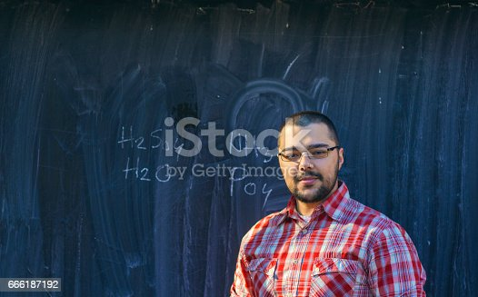926239360 istock photo Man standing in front of blackboard with chemical formula 666187192