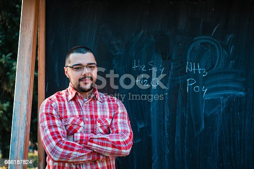 926239360 istock photo Man standing in front of blackboard with chemical formula 666187824