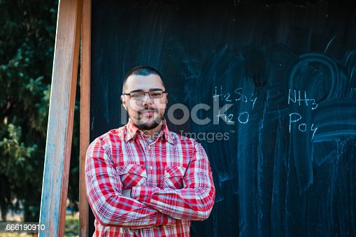 926239360 istock photo Man standing in front of blackboard with chemical formula 666190910